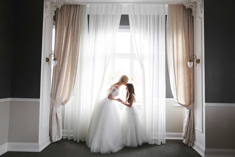 Bride and flower girl bridesmaid by window