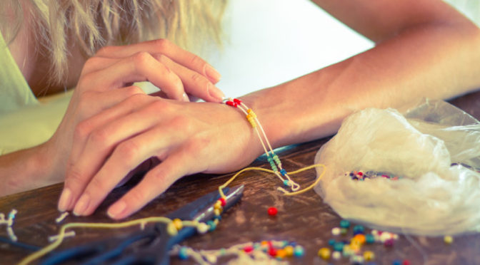 Woman hands making a bracelet with a rope and colorful beads, DIY fashion