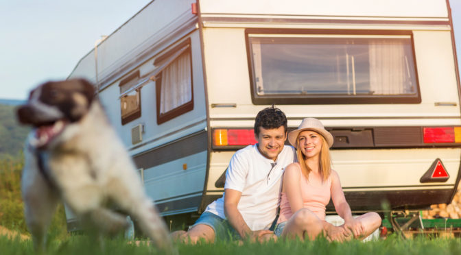 Beautiful young couple in front of a camper van on a summer day